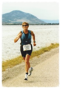 Valerie Gonzales running in an Ironman Canada race along the shore of Skaha Lake, BC